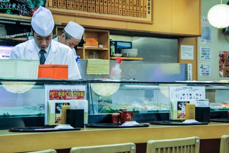 Kooktoestellen in de sushibar Een mensen kokende sushi en broodjes Nationaal voedsel van Japan stock fotografie