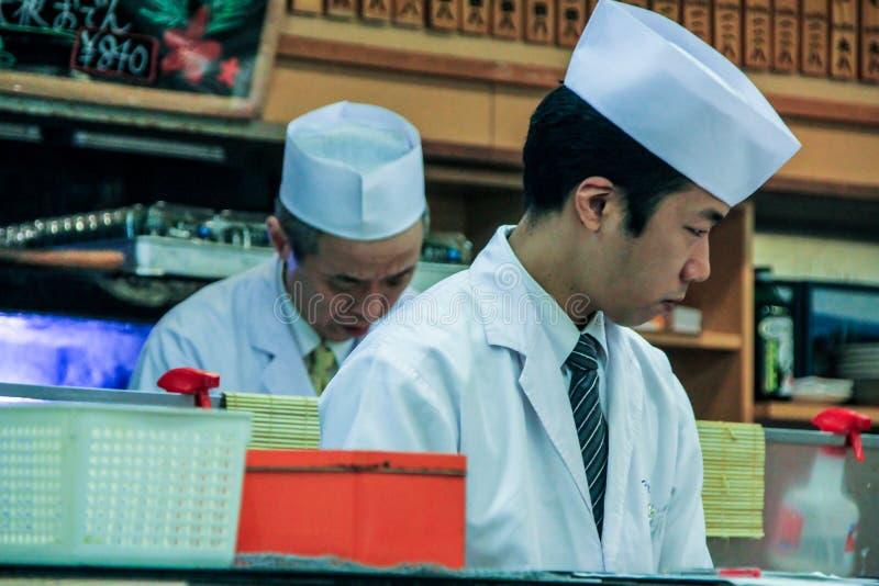 Kooktoestellen in de sushibar Een mensen kokende sushi en broodjes Nationaal voedsel van Japan stock foto's