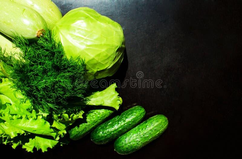Kool, sla, komkommers, courgette, dille op een zwarte achtergrond stock foto's