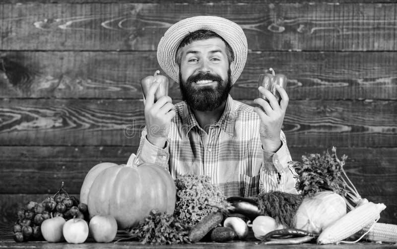 Koop verse inlandse groenten Mens met baard trots van zijn houten achtergrond van oogstgroenten Landbouwer met organisch stock foto