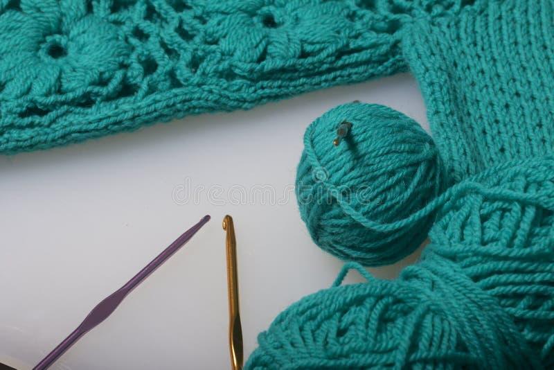 Koorden van draad voor het breien smaragdgroene kleur en haken voor het breien Lig op een klaar gebreid product stock fotografie