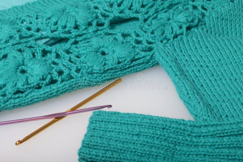 Koorden van draad voor het breien smaragdgroene kleur en haken voor het breien Lig op een klaar gebreid product royalty-vrije stock foto