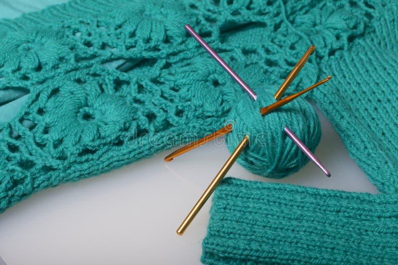 Koorden van draad voor het breien smaragdgroene kleur en haken voor het breien Lig op een klaar gebreid product stock foto's