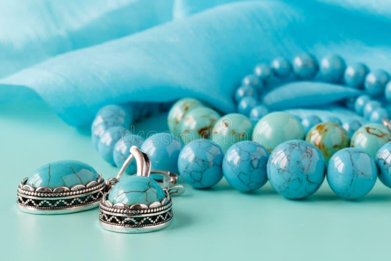 Koorden van turkooise parels op blauwe zijde als achtergrond royalty-vrije stock afbeelding