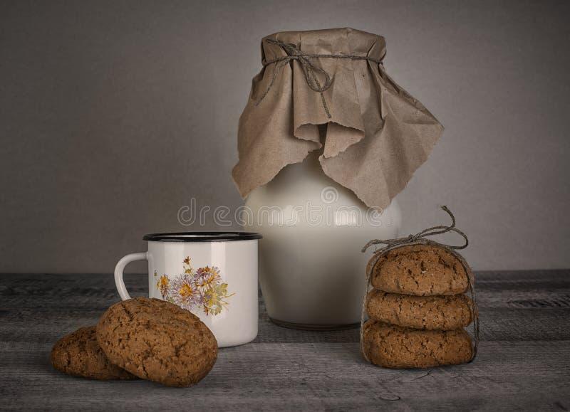 Kop en kruik van melk en eigengemaakte koekjes royalty-vrije stock foto