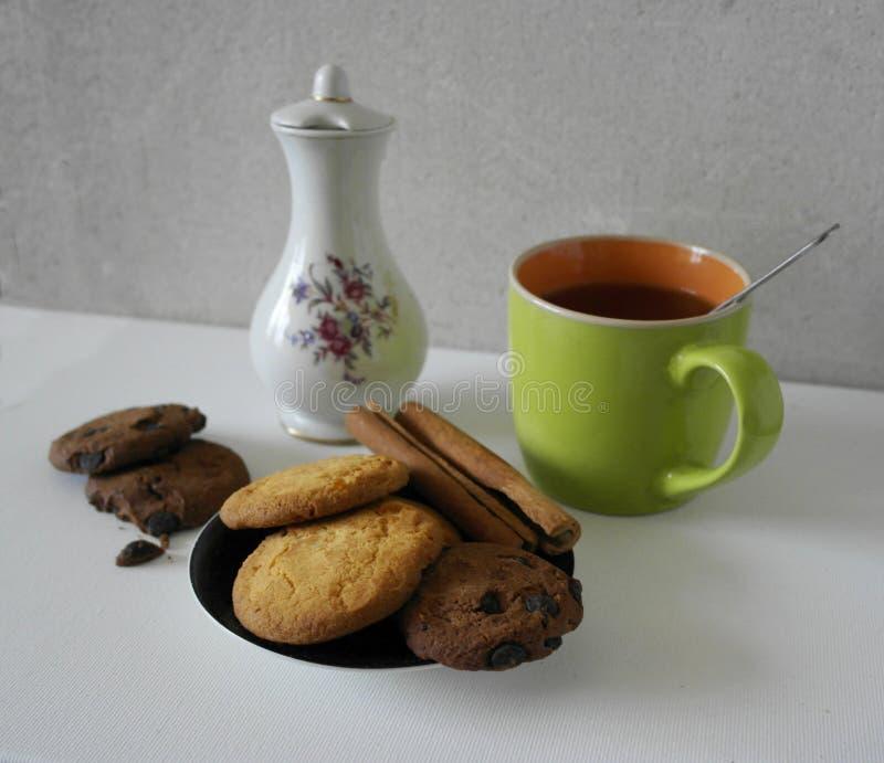 Kop en pot van koffie en koffiebonen, koekjes met kaneel, chocoladesuikergoed, op wit wordt geïsoleerd dat royalty-vrije stock foto