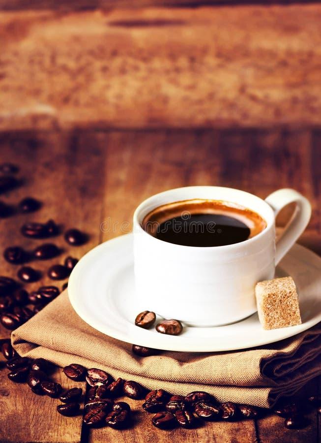Kop espresso met witte schotel en geroosterde koffiebonen op w stock foto