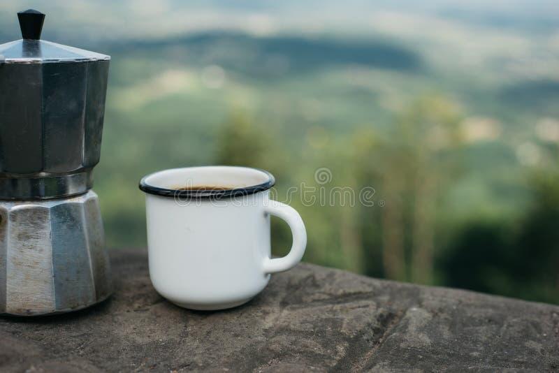 Kop heet koffie en koffiezetapparaat op achtergrond van aard royalty-vrije stock fotografie