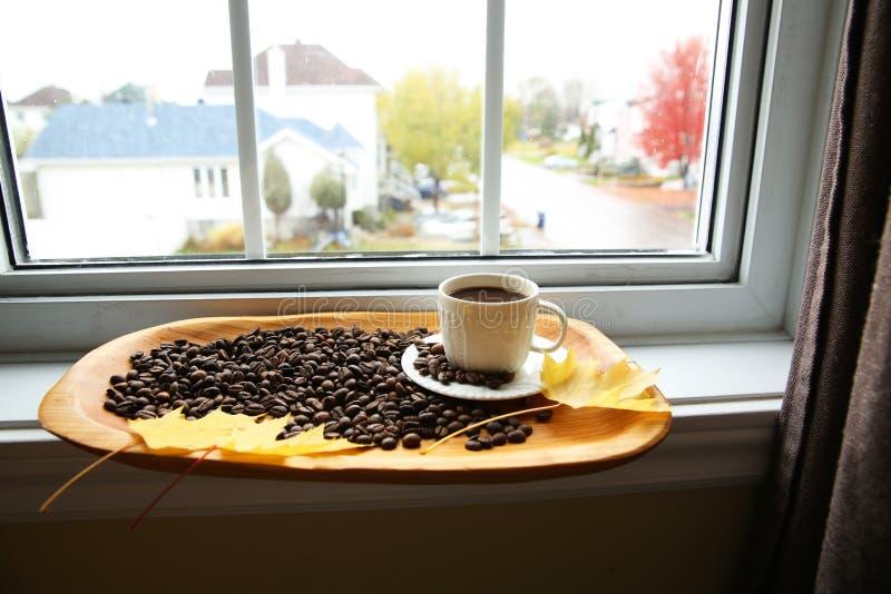 Kop koffie en bonen op houten achtergrond op venster royalty-vrije stock afbeeldingen