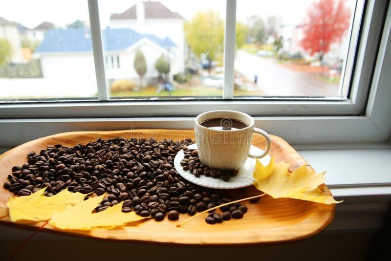Kop koffie en bonen op houten achtergrond op venster royalty-vrije stock foto's
