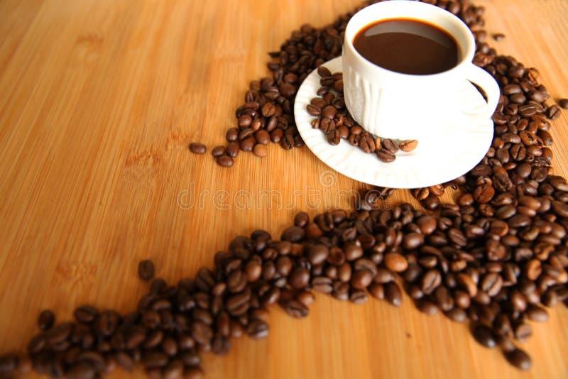 Kop koffie en elitebonen op houten lijst stock afbeeldingen
