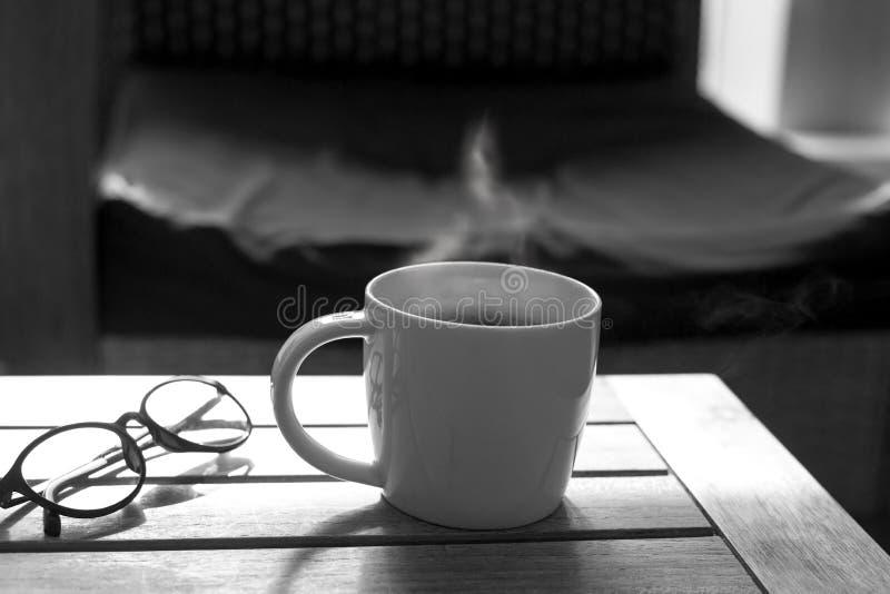 Kop koffie en glazen op houten lijst in het zonlicht stock foto