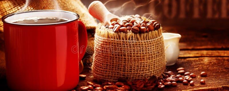 Kop koffie en koffiebonen in koffie het roosteren stock fotografie