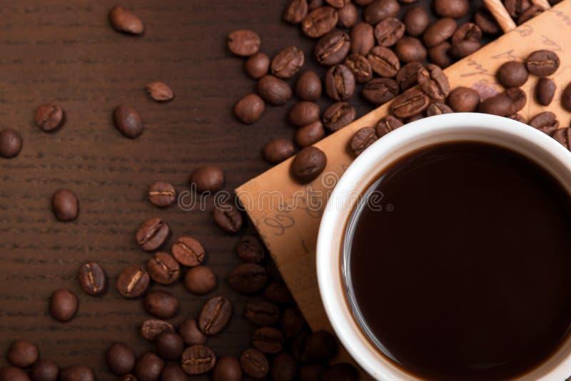 Kop koffie en koffiebonen op donkere bruine lijst royalty-vrije stock fotografie