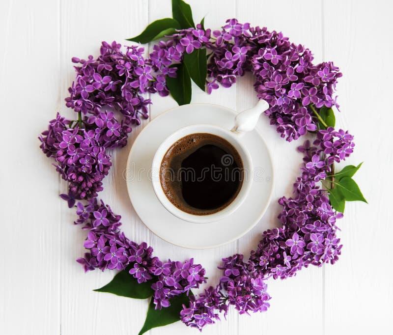 Kop koffie en lilac bloemen stock fotografie