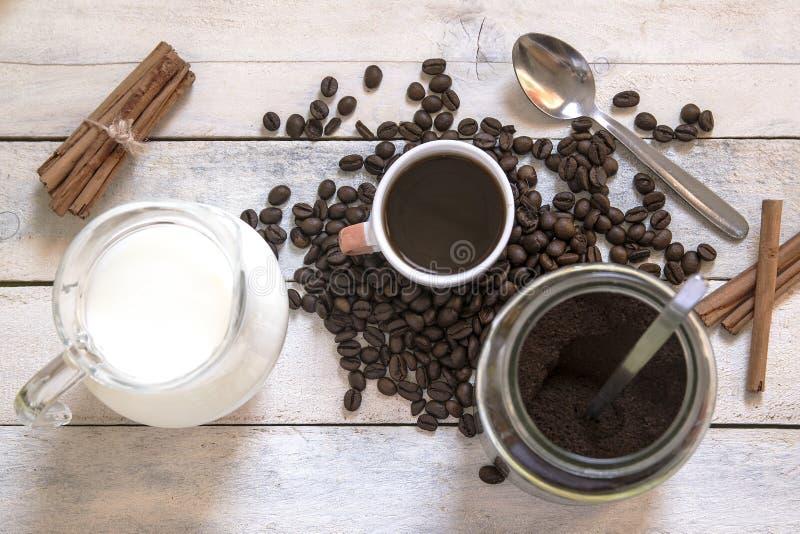 Kop koffie, melk, kaneel en sommige koffiebonen op een houten lijst in een rustieke keuken lege exemplaarruimte stock foto's