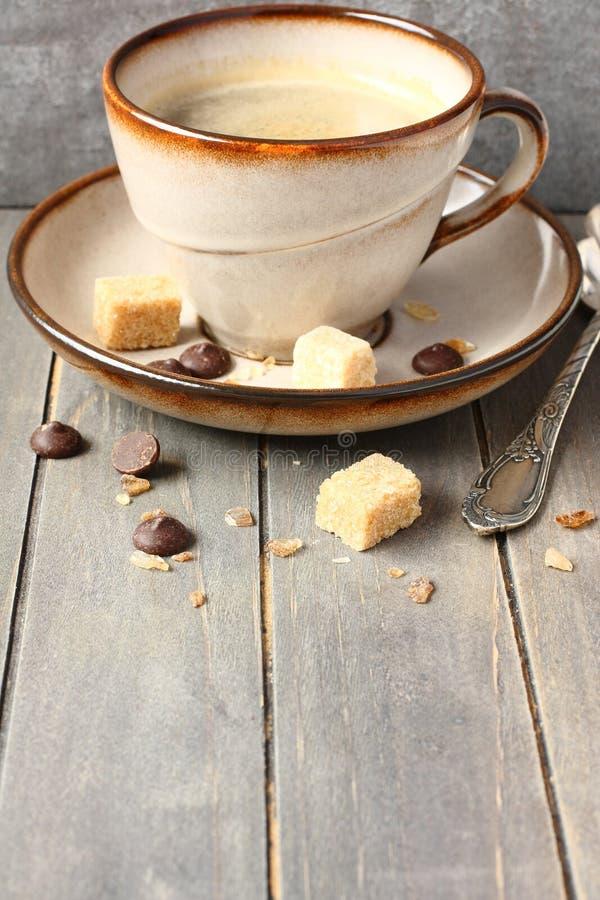 Kop koffie, suikerkubussen en chocoladedalingen op oude houten achtergrond met exemplaarruimte stock afbeeldingen