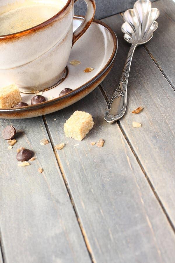 Kop koffie, suikerkubussen en chocoladedalingen op oude houten achtergrond met exemplaarruimte royalty-vrije stock afbeeldingen