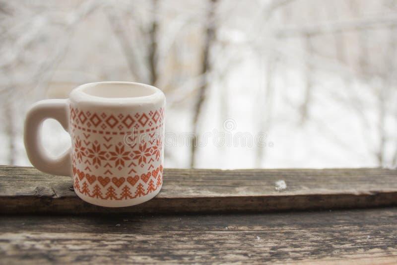 Kop met een patroon op een houten venstervensterbank in de winter royalty-vrije stock afbeelding