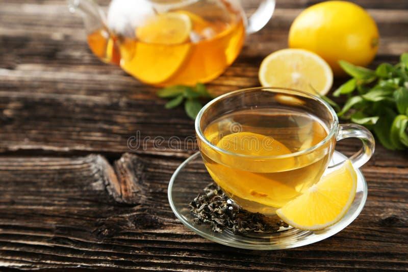 Kop met groene thee en theepot op de bruine houten achtergrond royalty-vrije stock foto