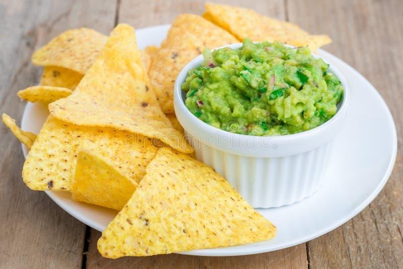Kop met guacamole met nachos wordt gediend die stock afbeeldingen