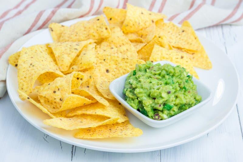 Kop met guacamole met nachos wordt gediend die stock fotografie