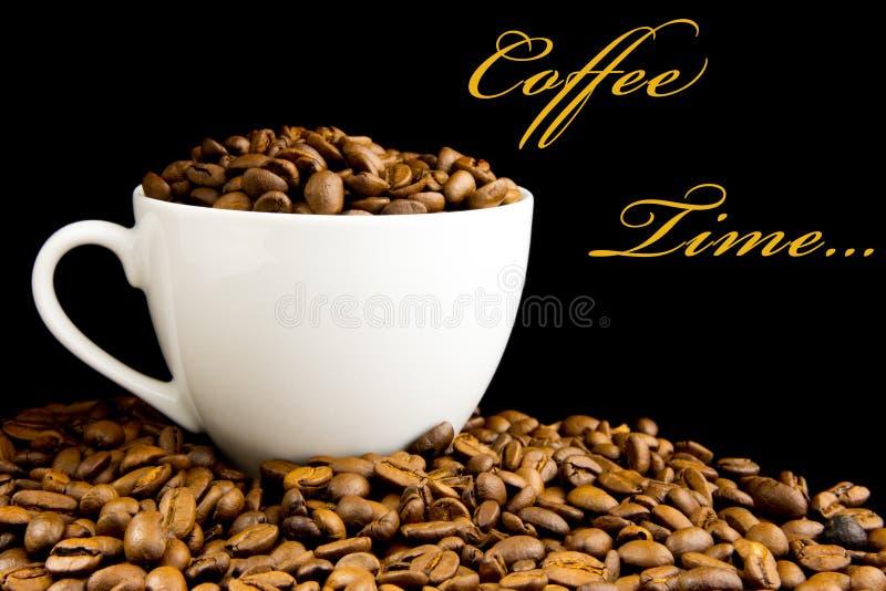 Kop met koffiebonen die wordt gevuld stock foto's