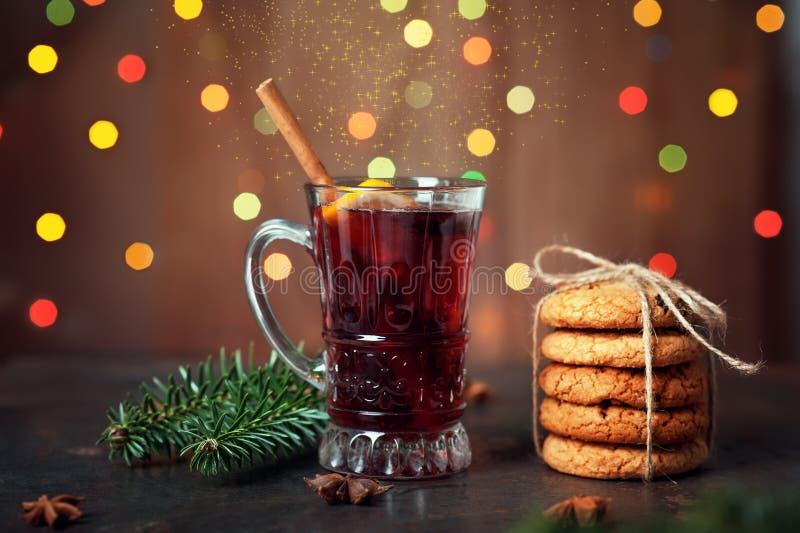 Kop met rode overwogen wijn of sangria en peperkoekkoekjes voor Kerstmisvakantie Magische drank op de achtergrond van lichtenkers stock afbeeldingen