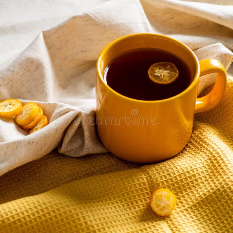 Kop met theekumquat op gele achtergrond stock foto