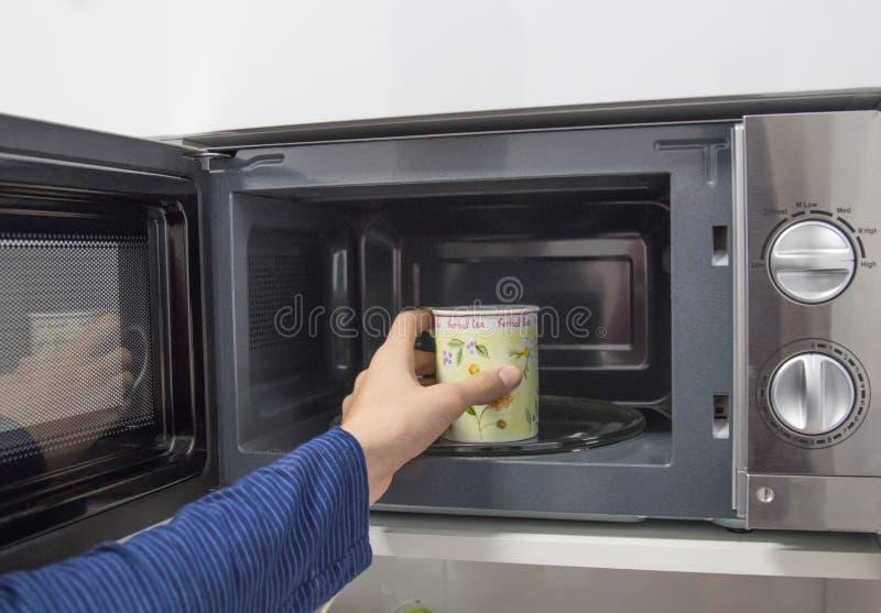 Kop in microgolfkoffie of infusies stock afbeelding