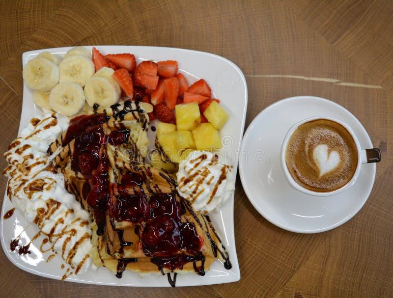 Kop schuimende cappuccino en wafels met fruit en room royalty-vrije stock afbeelding