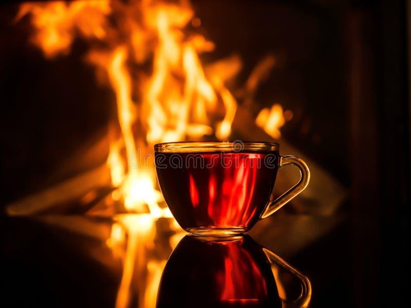 Kop thee door de open haard De Achtergrond van de brand royalty-vrije stock foto