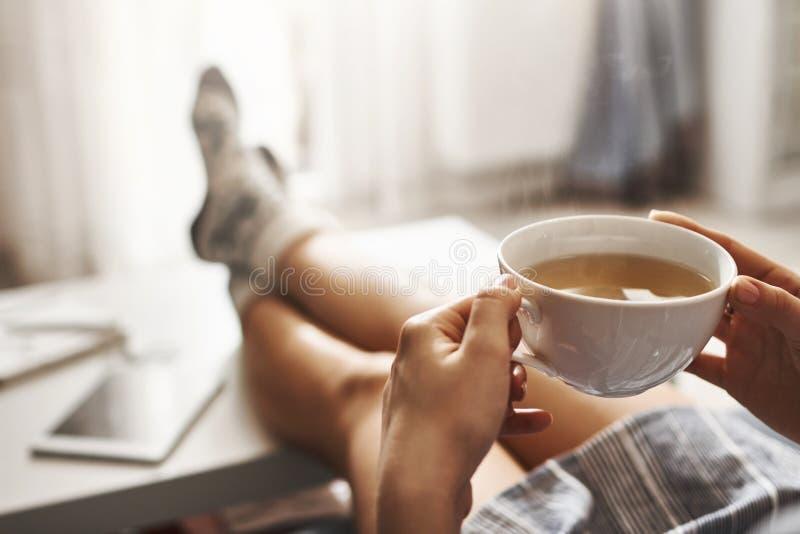 Kop thee en kou Vrouw die op laag liggen, benen op koffietafel houden, hete koffie drinken en van ochtend genieten stock foto