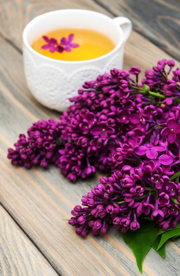 Kop thee en lilac bloemen stock afbeelding