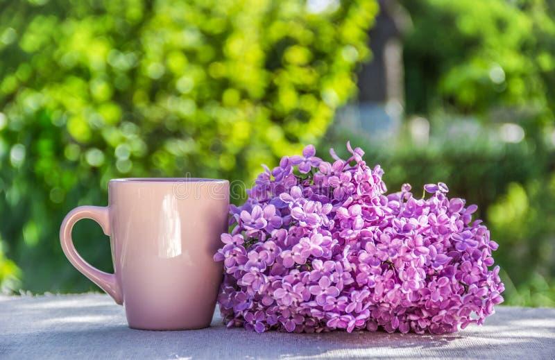 Kop thee en sering Doorboor mok De kop van de thee in de tuin stock afbeelding