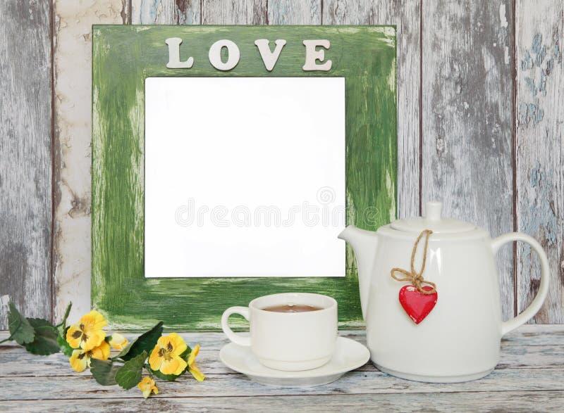 Kop thee en theepot met hartvorm op houten lijst stock fotografie