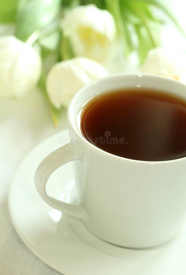 Kop thee en witte tulpen stock afbeeldingen
