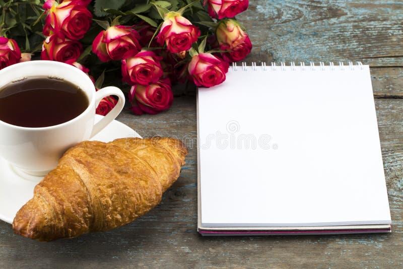Kop thee met croissant, verse rozen, en notitieboekjeblad van p stock fotografie