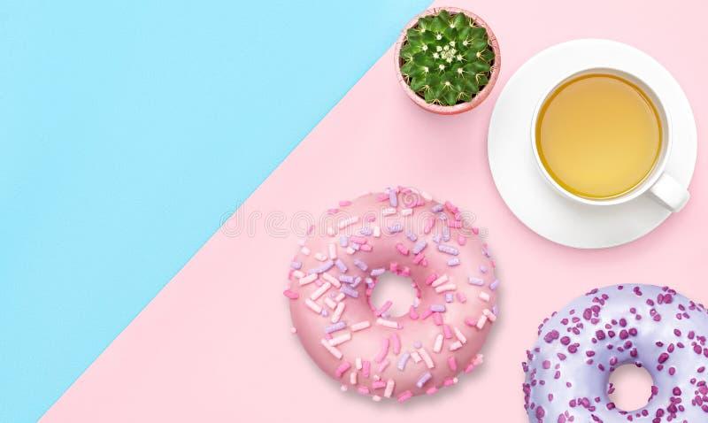 Kop thee met donuts op roze en blauwe pastelkleurachtergrond Hoogste mening Vlak leg zoet voedselconcept Ontbijt met dessert royalty-vrije stock afbeelding