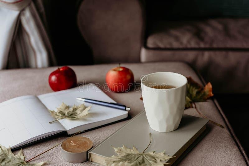 Kop thee met een boek in het binnenland met de herfstblad, noteboo stock afbeelding