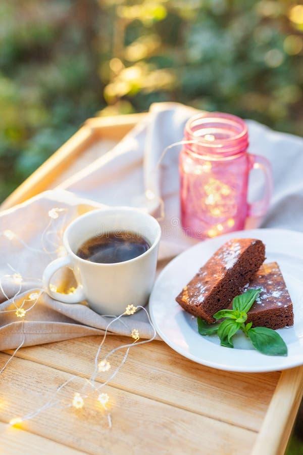 Kop thee met een browniecake met munt op een houten die dienblad wordt met mooie lichten in openlucht wordt verfraaid verfraaid d stock foto's