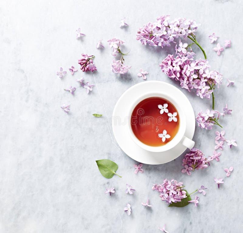 Kop thee met lilac bloemen op marmeren achtergrond stock foto's
