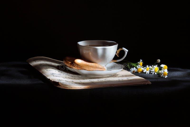 Kop thee met madeliefjes stock foto's