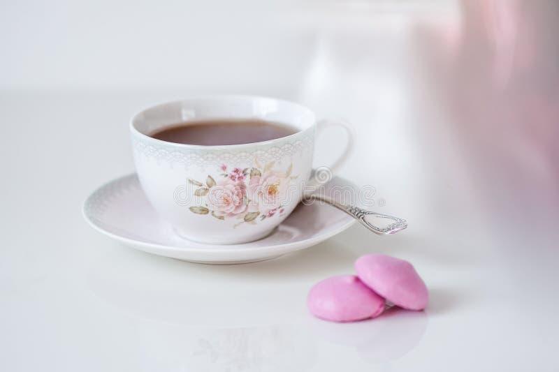 Kop thee met roze schuimgebakjes op een witte achtergrond De kaart van de vakantie stock afbeeldingen