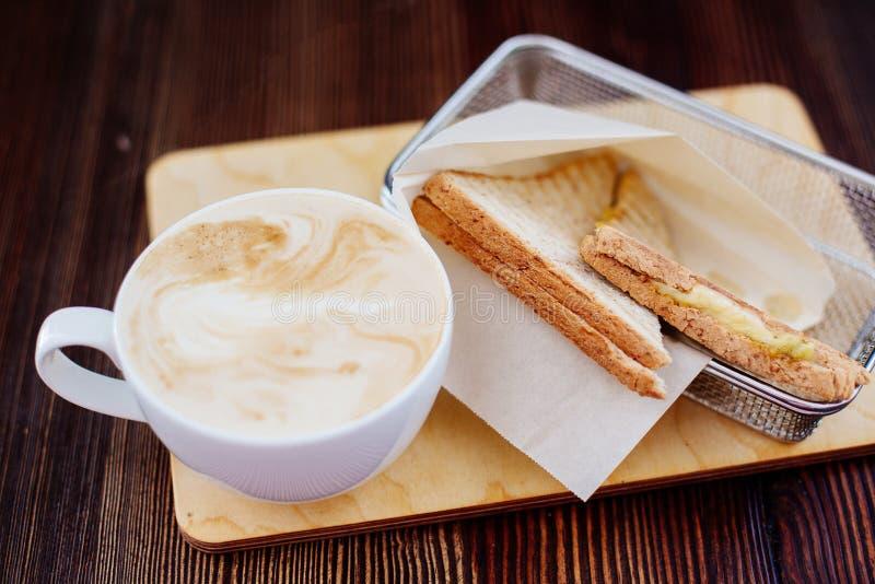 Kop van cappuccino en een sandwich stock afbeelding