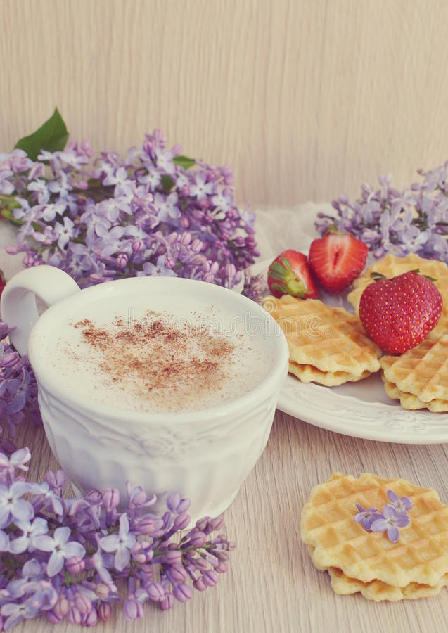Kop van cappuccino met wafels, aardbeien en bloemen royalty-vrije stock foto's