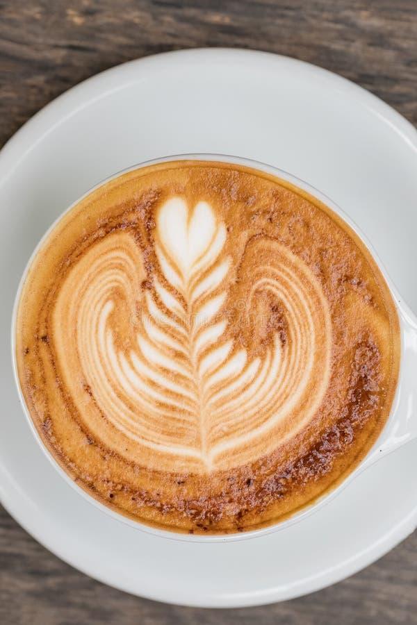 Kop van cappuccinokoffie met mooie die lattekunst op houten lijst wordt gediend stock afbeeldingen