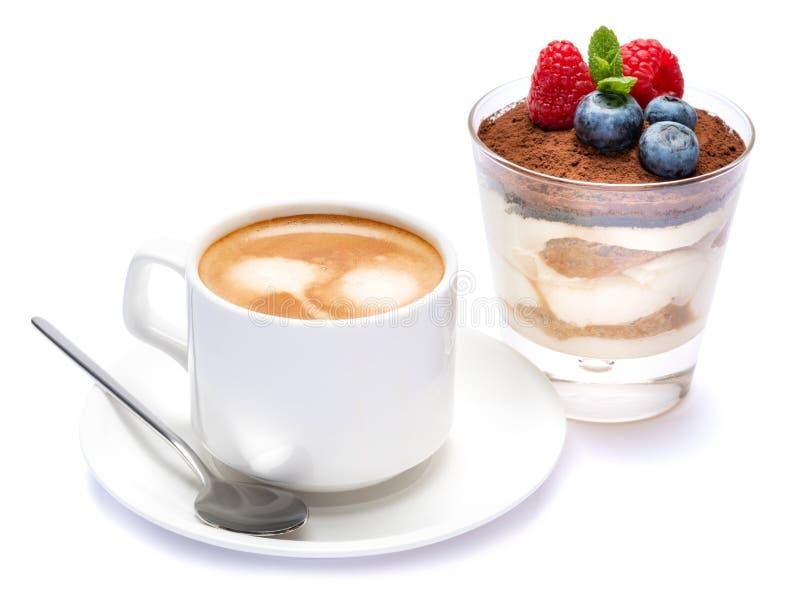 Kop van cofee en Klassiek die tiramisudessert met bosbessen en frambozen in een glas op een witte achtergrond wordt geïsoleerd royalty-vrije stock foto