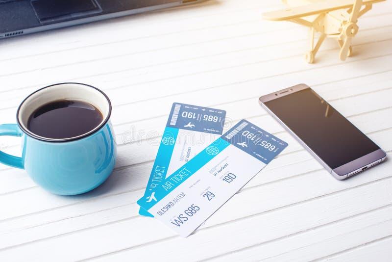 Kop van de kaartjes, de telefoon en laptop van het koffievliegtuig op witte houten achtergrond Concept het kopen van het online k royalty-vrije stock foto's