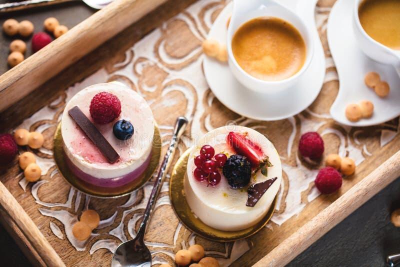 Kop van espresso met zoete cakes met bessen op lijst stock fotografie